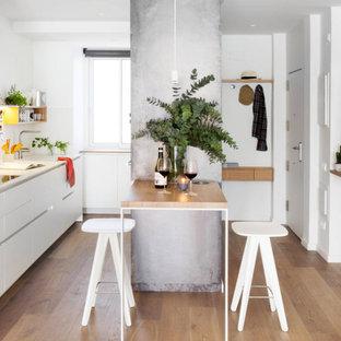 Foto di una cucina parallela minimal con lavello sottopiano, ante lisce, ante bianche, pavimento in legno massello medio, penisola, pavimento marrone e top bianco