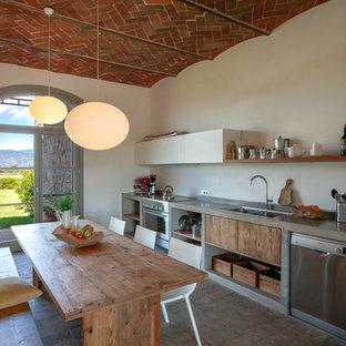 Ispirazione per una cucina mediterranea con lavello da incasso, ante lisce, ante in legno scuro, top in cemento, elettrodomestici in acciaio inossidabile, nessuna isola, pavimento marrone e top grigio
