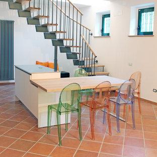 他の地域の中くらいのモダンスタイルのおしゃれなキッチン (ダブルシンク、フラットパネル扉のキャビネット、白いキャビネット、ステンレスカウンター、黒いキッチンパネル、シルバーの調理設備、テラコッタタイルの床、ピンクの床) の写真