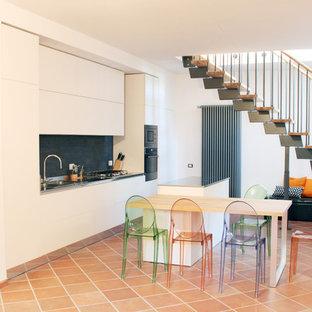 Zweizeilige, Mittelgroße Moderne Wohnküche mit Doppelwaschbecken, flächenbündigen Schrankfronten, weißen Schränken, Edelstahl-Arbeitsplatte, Küchenrückwand in Schwarz, Küchengeräten aus Edelstahl, Terrakottaboden, Kücheninsel und rosa Boden in Sonstige