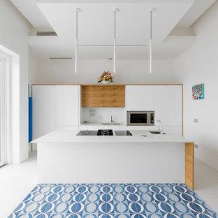 Ispirazione per una cucina parallela minimal con lavello sottopiano, ante lisce, ante bianche, elettrodomestici neri, isola, pavimento multicolore e top bianco