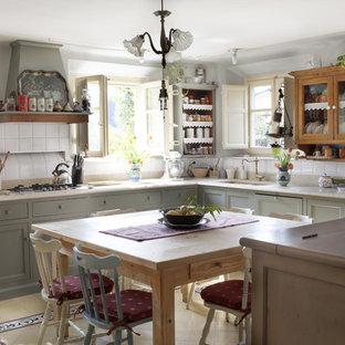 フィレンツェのカントリー風おしゃれなキッチン (アンダーカウンターシンク、落し込みパネル扉のキャビネット、グレーのキャビネット、白いキッチンパネル、アイランドなし、マルチカラーの床、白いキッチンカウンター) の写真