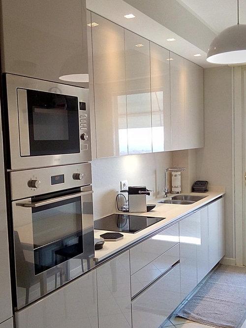 Cucina laccata lucida ecrù, sagomata e chiusa da un cartongesso.