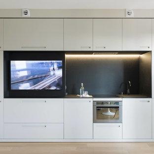 Esempio di una cucina lineare design con ante lisce, ante bianche, paraspruzzi nero, elettrodomestici da incasso, parquet chiaro, nessuna isola, pavimento beige e top nero