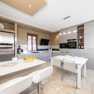 Foto di una piccola cucina minimal con lavello a vasca singola, ante lisce, ante grigie, paraspruzzi bianco, elettrodomestici in acciaio inossidabile e penisola