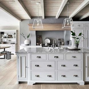 Immagine di una grande cucina tradizionale con ante bianche, lavello stile country, ante a filo, top in marmo, paraspruzzi grigio, parquet chiaro e top grigio