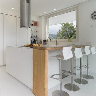 Immagine di una cucina minimal con ante lisce, ante bianche e pavimento bianco