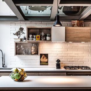 Bild på ett industriellt vit vitt parallellkök, med en undermonterad diskho, släta luckor, skåp i mellenmörkt trä, vitt stänkskydd, stänkskydd i tegel, svarta vitvaror och en köksö
