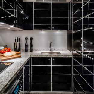 Foto di una cucina ad U contemporanea di medie dimensioni e chiusa con lavello sottopiano, ante lisce, ante nere, top in granito, paraspruzzi grigio, elettrodomestici neri, pavimento grigio e nessuna isola