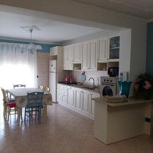 カターニア/パルレモの中サイズのシャビーシック調のおしゃれなキッチン (ドロップインシンク、落し込みパネル扉のキャビネット、ベージュのキャビネット、クオーツストーンカウンター、ベージュキッチンパネル、セラミックタイルのキッチンパネル、カラー調理設備、セラミックタイルの床、オレンジの床) の写真