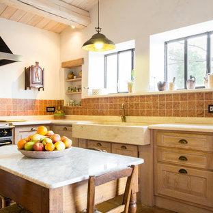 Ispirazione per una cucina country con ante con bugna sagomata, ante in legno chiaro, isola, lavello stile country, paraspruzzi rosso, elettrodomestici neri e top beige