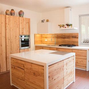 Große Nordische Küche in L-Form mit flächenbündigen Schrankfronten, hellen Holzschränken, Terrakottaboden, Kücheninsel, Doppelwaschbecken, Marmor-Arbeitsplatte, Küchenrückwand in Weiß, Glasrückwand und schwarzen Elektrogeräten in Venedig