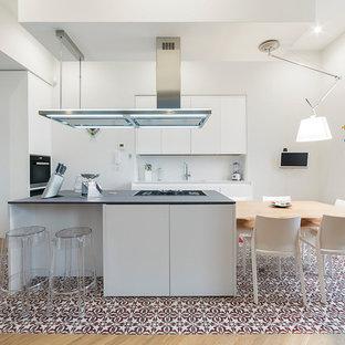 Foto di una cucina contemporanea con ante lisce, ante bianche, paraspruzzi bianco, paraspruzzi con lastra di vetro, elettrodomestici in acciaio inossidabile, pavimento con piastrelle in ceramica, pavimento multicolore e top grigio