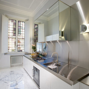 Foto di una cucina lineare minimal chiusa e di medie dimensioni con lavello integrato, ante lisce, ante bianche, top in acciaio inossidabile, paraspruzzi a effetto metallico, paraspruzzi con piastrelle di metallo, elettrodomestici in acciaio inossidabile e pavimento in marmo
