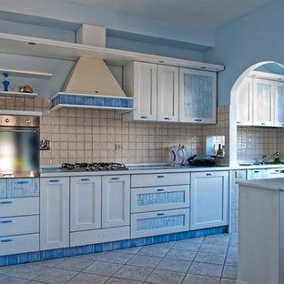 Mittelgroße, Offene, Einzeilige Mediterrane Küche mit Einbauwaschbecken, profilierten Schrankfronten, weißen Schränken, Arbeitsplatte aus Fliesen, Rückwand aus Keramikfliesen, Küchengeräten aus Edelstahl, Keramikboden und Kücheninsel in Rom