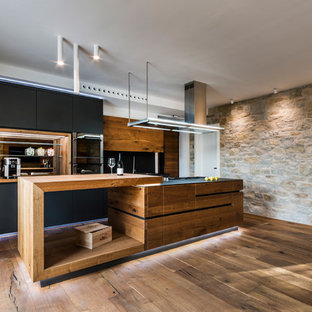Modelo de cocina lineal, contemporánea, grande, abierta, con fregadero encastrado, puertas de armario negras, encimera de madera, salpicadero negro, salpicadero de pizarra, suelo de madera en tonos medios, una isla y armarios con paneles lisos