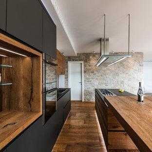 Cette image montre une cuisine ouverte rustique avec un évier posé, des portes de placard noires, un plan de travail en bois, une crédence noire, une crédence en ardoise, un sol en bois brun et un îlot central.