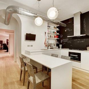 Foto di una cucina a L minimal con ante lisce, ante bianche, parquet chiaro e penisola