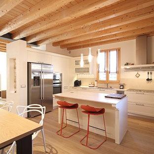 Стильный дизайн: п-образная кухня-гостиная в современном стиле с врезной раковиной, фасадами в стиле шейкер, белыми фасадами, бежевым фартуком, техникой из нержавеющей стали, паркетным полом среднего тона и островом - последний тренд
