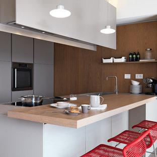 Esempio di una cucina parallela minimal con lavello integrato, ante lisce, ante grigie, top in legno, elettrodomestici in acciaio inossidabile, penisola, top marrone, paraspruzzi marrone e paraspruzzi a finestra