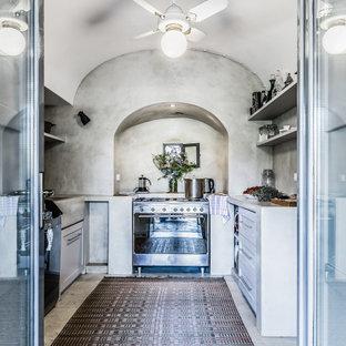 Ispirazione per una cucina ad U mediterranea di medie dimensioni con lavello integrato, ante in stile shaker, ante bianche, paraspruzzi grigio, elettrodomestici in acciaio inossidabile, nessuna isola, pavimento grigio e top grigio