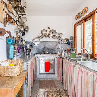 Immagine di una cucina ad U mediterranea chiusa e di medie dimensioni con lavello da incasso, nessun'anta, top in cemento, paraspruzzi grigio, elettrodomestici in acciaio inossidabile, pavimento in cemento, pavimento grigio e nessuna isola