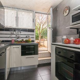 Esempio di una piccola cucina ad U design con ante lisce, ante nere, paraspruzzi bianco, elettrodomestici neri e pavimento grigio