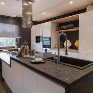 Immagine di una cucina parallela design di medie dimensioni con lavello da incasso, ante lisce, ante bianche, paraspruzzi nero, paraspruzzi in gres porcellanato, elettrodomestici neri, penisola, pavimento grigio e top nero