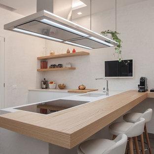 Foto di una cucina a L contemporanea con lavello sottopiano, ante lisce, ante bianche, penisola e top bianco