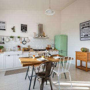Свежая идея для дизайна: линейная кухня среднего размера в стиле кантри с обеденным столом, раковиной в стиле кантри, фасадами в стиле шейкер, белыми фасадами, столешницей из дерева, белым фартуком, фартуком из плитки кабанчик, цветной техникой, серым полом и бежевой столешницей без острова - отличное фото интерьера