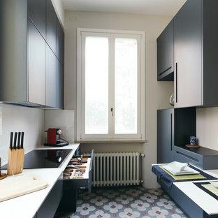 Ispirazione per una cucina parallela minimal di medie dimensioni con ante lisce, ante blu, paraspruzzi bianco, pavimento con piastrelle in ceramica, pavimento multicolore e paraspruzzi con lastra di vetro