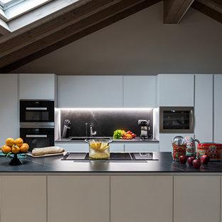 Foto di una cucina minimal di medie dimensioni con lavello integrato, ante lisce, ante bianche, paraspruzzi nero, elettrodomestici da incasso e top nero