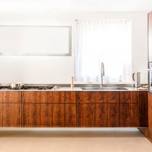 Photo of a small country eat-in kitchen in Other with an integrated sink, flat-panel cabinets, dark wood cabinets, stainless steel benchtops, stainless steel appliances, terra-cotta floors and pink floor.