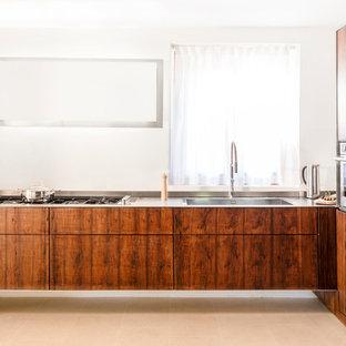 Imagen de cocina comedor campestre, pequeña, con fregadero integrado, armarios con paneles lisos, puertas de armario de madera en tonos medios, encimera de acero inoxidable, electrodomésticos de acero inoxidable, suelo de baldosas de terracota y suelo rosa