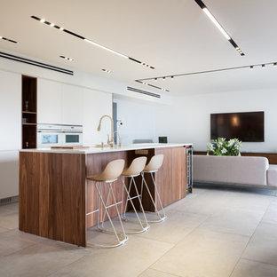 ミラノの大きいコンテンポラリースタイルのおしゃれなキッチン (フラットパネル扉のキャビネット、白い調理設備、グレーの床、白いキッチンカウンター、中間色木目調キャビネット) の写真