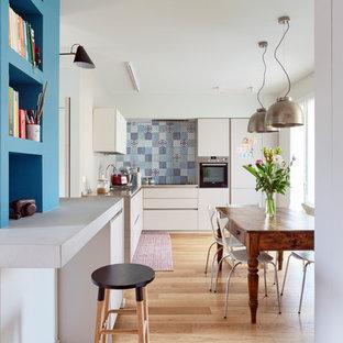 Idee per una cucina bohémian con ante lisce, ante bianche, paraspruzzi multicolore, elettrodomestici in acciaio inossidabile, parquet chiaro e pavimento beige