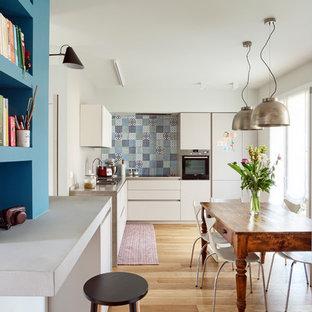 他の地域のエクレクティックスタイルのおしゃれなキッチン (ダブルシンク、フラットパネル扉のキャビネット、白いキャビネット、マルチカラーのキッチンパネル、パネルと同色の調理設備、無垢フローリング、アイランドなし、茶色い床、茶色いキッチンカウンター) の写真