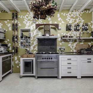 Ispirazione per una cucina a L bohémian chiusa e di medie dimensioni con ante a filo, ante bianche, top in acciaio inossidabile, elettrodomestici in acciaio inossidabile e pavimento in cemento