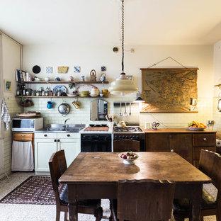 Esempio di una cucina eclettica con lavello a doppia vasca, ante lisce, ante in legno bruno, paraspruzzi bianco, paraspruzzi con piastrelle diamantate, elettrodomestici neri, nessuna isola e pavimento grigio