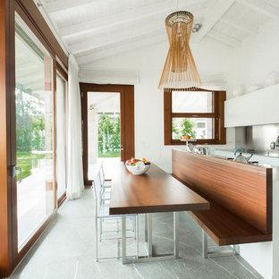 Inredning av ett modernt stort kök, med vita skåp, stänkskydd med metallisk yta, en köksö, en integrerad diskho, släta luckor, bänkskiva i koppar, stänkskydd i metallkakel och marmorgolv