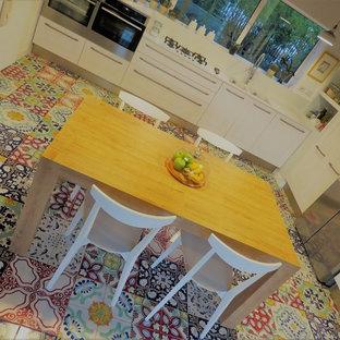 ナポリの広いコンテンポラリースタイルのおしゃれなキッチン (アンダーカウンターシンク、フラットパネル扉のキャビネット、淡色木目調キャビネット、オニキスカウンター、白いキッチンパネル、木材のキッチンパネル、シルバーの調理設備、セラミックタイルの床、マルチカラーの床) の写真