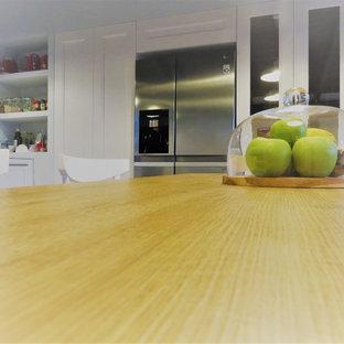 ナポリの大きいコンテンポラリースタイルのおしゃれなキッチン (アンダーカウンターシンク、フラットパネル扉のキャビネット、淡色木目調キャビネット、オニキスカウンター、白いキッチンパネル、木材のキッチンパネル、シルバーの調理設備の、セラミックタイルの床、マルチカラーの床) の写真