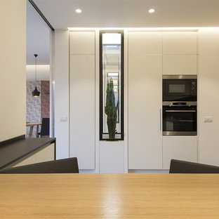 Photo of an expansive modern u-shaped open plan kitchen in Rome with a drop-in sink, beaded inset cabinets, quartz benchtops, black splashback, slate splashback, stainless steel appliances, porcelain floors, grey floor and black benchtop.