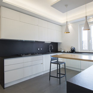 Expansive modern u-shaped open plan kitchen in Rome with a drop-in sink, beaded inset cabinets, quartz benchtops, black splashback, slate splashback, stainless steel appliances, porcelain floors, grey floor and black benchtop.