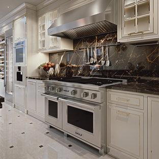 Modelo de cocina en L y bandeja, contemporánea, de tamaño medio, cerrada, con fregadero bajoencimera, armarios con paneles lisos, puertas de armario blancas, encimera de mármol, salpicadero negro, salpicadero de mármol, electrodomésticos de acero inoxidable, suelo de mármol, una isla, suelo blanco y encimeras negras