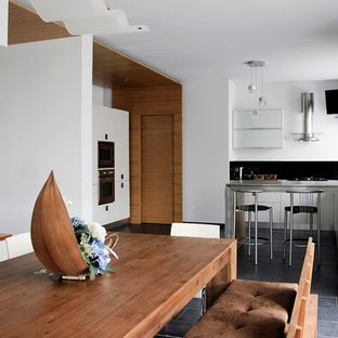 This is an example of a mid-sized modern l-shaped open plan kitchen in Other with with island, a drop-in sink, light wood cabinets, limestone benchtops, black splashback, glass sheet splashback, stainless steel appliances, ceramic floors and black floor.