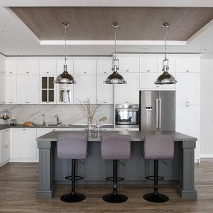 Свежая идея для дизайна: большая угловая кухня-гостиная в стиле неоклассика (современная классика) с одинарной раковиной, фасадами с утопленной филенкой, белыми фасадами, столешницей из ламината, белым фартуком, фартуком из керамогранитной плитки, техникой из нержавеющей стали, полом из керамогранита, островом, серым полом и серой столешницей в частном доме - отличное фото интерьера