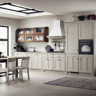 This is an example of a mid-sized shabby-chic style single-wall open plan kitchen in Other with a single-bowl sink, recessed-panel cabinets, white cabinets, laminate benchtops, no island, black appliances and grey benchtop.