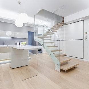 Esempio di una cucina a L minimalista con ante lisce, ante beige, parquet chiaro, un'isola, pavimento beige e top bianco
