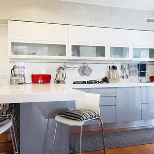 Ispirazione per una cucina a L design con ante lisce, ante bianche, paraspruzzi bianco, penisola, top bianco e pavimento in legno massello medio